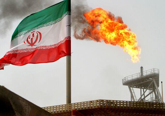 علم إيران على خلفية توهج ناري لغاز في حقل سوروش النفطي في الخليج الفارسي، إيران 25 يوليو/ تموز 2018