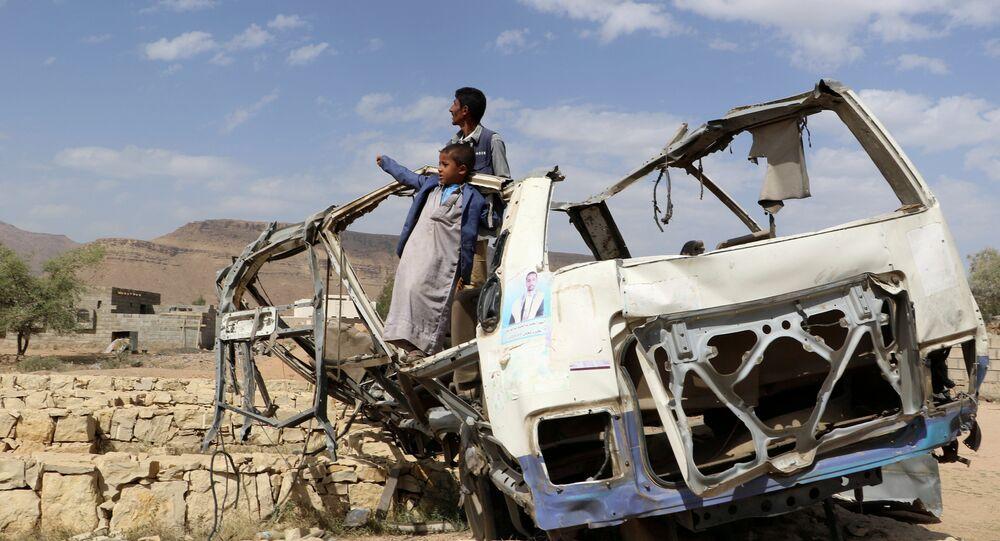 أطفال يقفون على حافلة تعرضت للدمار في صعدة - اليمن