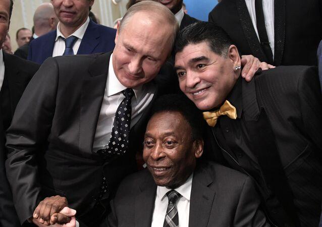 الرئيس فلاديمير بوتين خلال اللقاء مع نجوم كرة القدم: لاعب كرة القدم بيليه، ولاعب كرة القدم البرازيلي دييغو مارادونا،  قبل بدء القرعة النهائية لكأس العالم روسيا - 2018