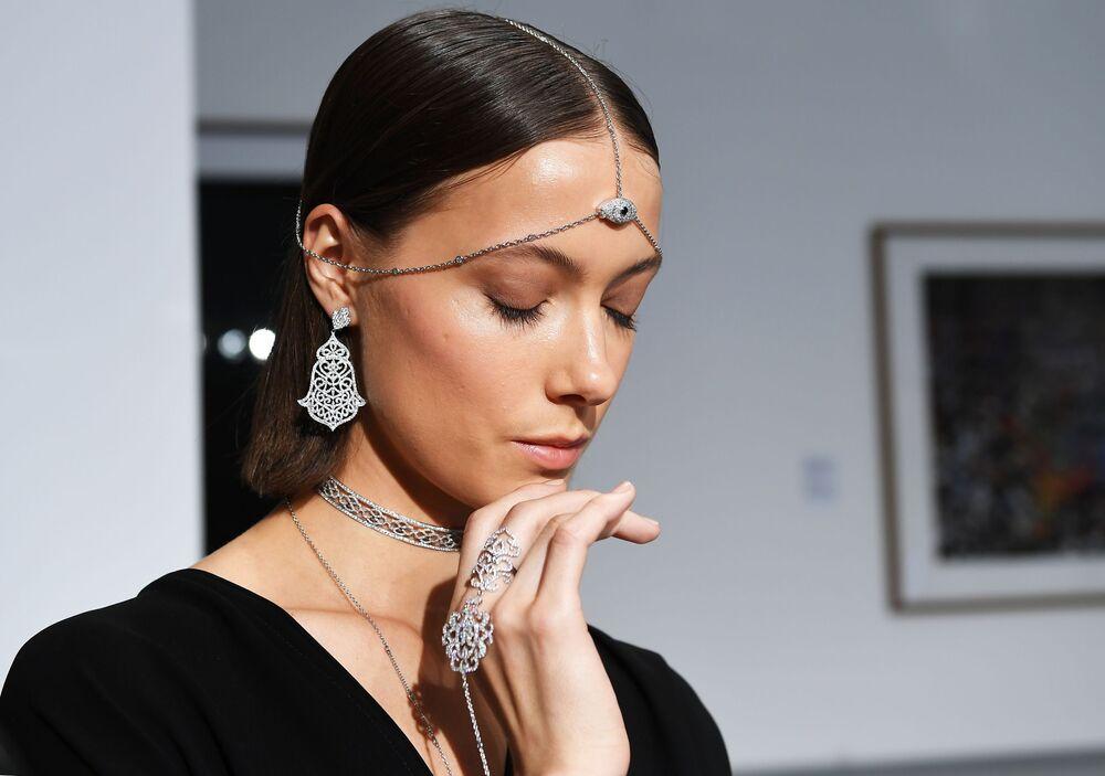 عارضة أزياء تقدم مجوهرات لدار المجوهرات Noudar بمعرض فصول قطر بمتحف لفنون الوسائط المتعددة في موسكو