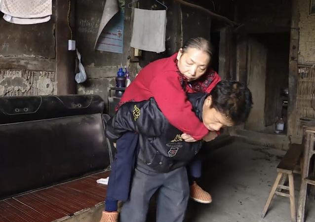 Стоп-кадр из видео о китайце, который в течении 15 лет носит свою парализованную мать на спине
