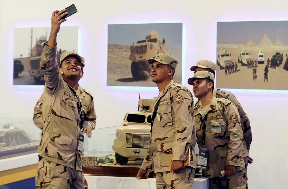 جنود مصريون يلتقطون صورة سيلفي على خلفية الجناح المصري في معرض إيديكس 2018 في القاهرة، 3 ديسمبر/ كانون الأول 2018