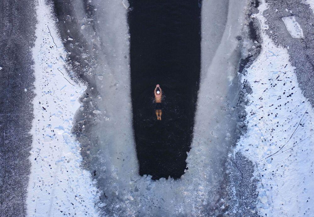 رجل يسبح في بحيرة شنيانغ بمحافظة لياونينغ، الصين 10 ديسمبر/ كانون الأول 2018