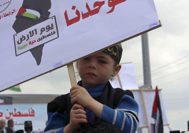 طفل فلسطيني يحمل لافتة الأرض توحدنا، فلسطين أرض عربية، خلال مسيرة بمناسبة يوم الأرض في بيت حانون، بالقرب من حدود القطاع مع إسرائيل 30 مارس/ آذار 2016