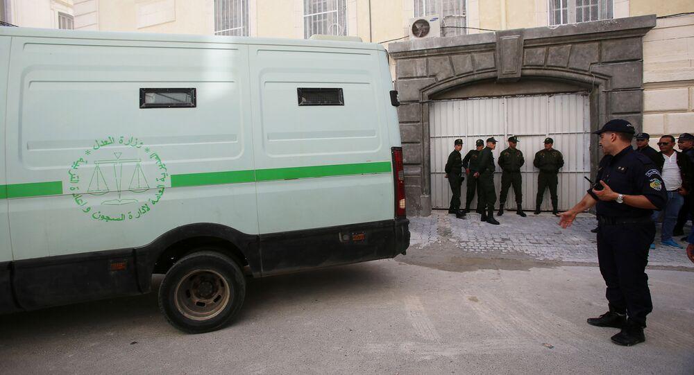 ضباط الشرطة بالقرب من سيارة نقل السجناء عند بوابة المحكمة بعد أن تم نقل أحد رجال الأعمال المشتبه بهم في الجزائر العاصمة