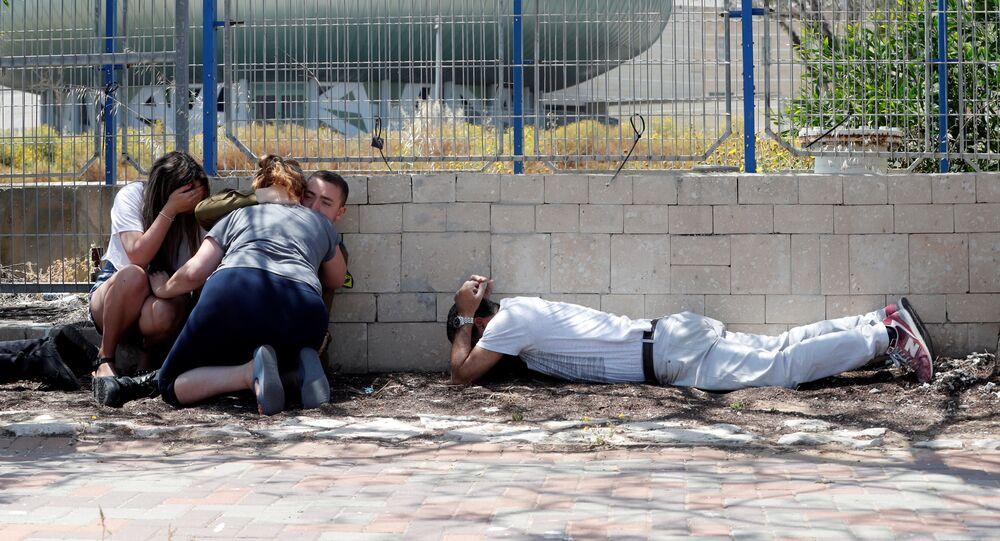 إسرائيليون يستترون وهم يسمعون صفارات الإنذار تحذر من الصواريخ القادمة من غزة في مدينة عسقلان جنوبي إسرائيل