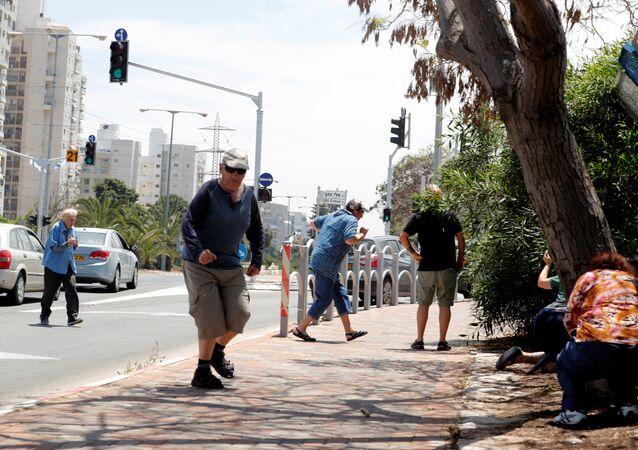 إسرائيليون يركضون للاحتماء وهم يسمعون صفارات الإنذار تحذر من الصواريخ القادمة من غزة في مدينة عسقلان جنوبي إسرائيل