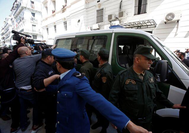 وسائل الإعلام والشرطة تحيط بقافلة من مركبات الشرطة بينما يتم نقل رجل أعمال مشتبه به إلى المحكمة في الجزائر