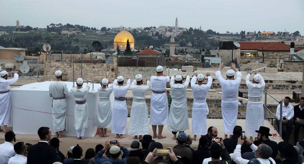 قبة الصخرة في الخلفية بينما يشارك رجال يهوديون أرثوذكس في احتفال عيد الفصح في القدس