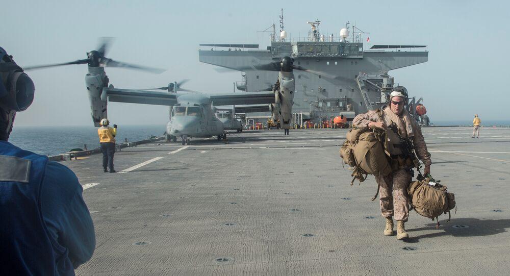 فرد من مشاة البحرية الأمريكية يحمل معداته على سطح حاملة الطائرات يو إس إس لويس ب. بولر في الخليج العربي