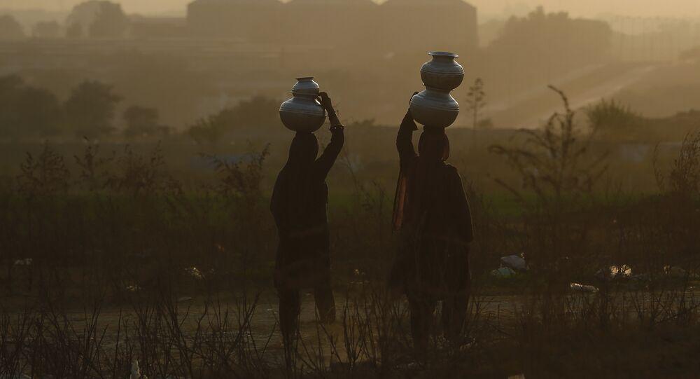 باكستانيات يحملن المياه إلى منازلهن في أمسية ضبابية على مشارف إسلام أباد
