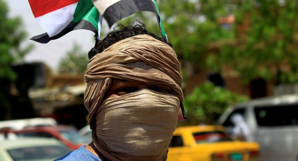 عضو في تحالف المعارضة والمجموعات الاحتجاجية في السودان يرتدي العلم الوطني وهو يهتف بشعارات خارج البنك المركزي السوداني