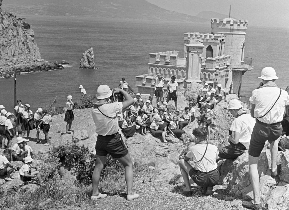 تلاميذ ومدرسون يلتقطون صورا جماعية على خلفية قصر السنونو على جرف صخري في القرم، في مخيم عموم الاتحاد السوفيتي أرتيك باسم ف. إ. لينين، 1958