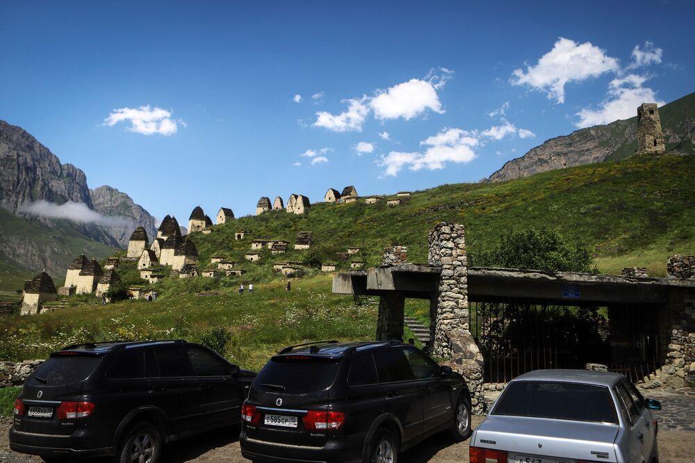 سيارات السياح متوقفة بالقرب من المقبرة في إقليم مدينة الموتى في جمهورية أوسيتيا الشمالية الروسية