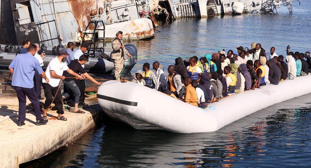 خفر السواحل الليبي يقوم بسحب قارب يحمل مهاجرين أفارقة، تم إنقاذهم أثناء محاولتهم الوصول إلى أوروبا بطريقة غير شرعية، في قاعدة بحرية بالقرب من العاصمة طرابلس في 29 سبتمبر/ أيلول 2015.