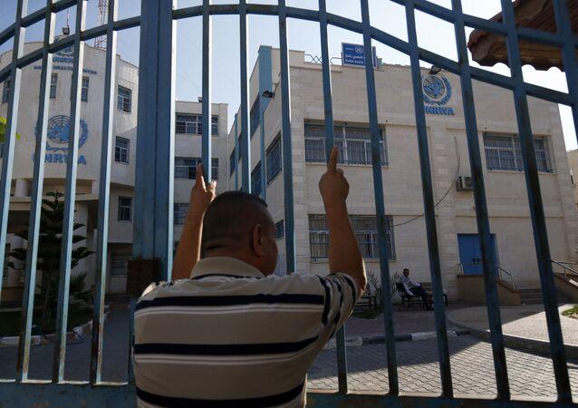 رجل فلسطيني يقف خارج البوابة المغلقة لوكالة غوث وتشغيل اللاجئين الفلسطينيين (الأونروا)