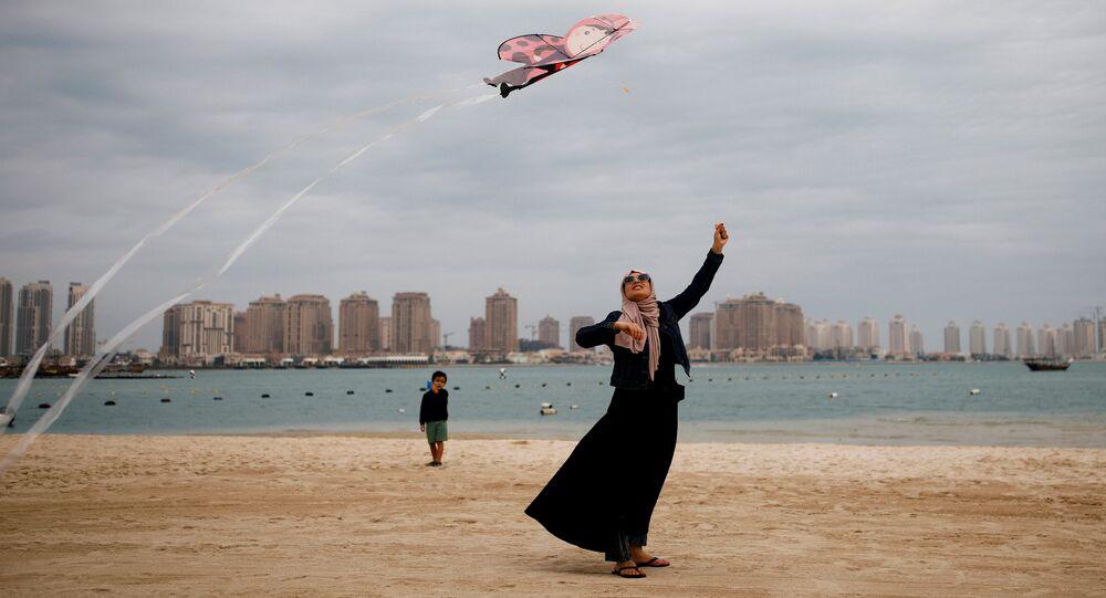 امرأة تطلق طيقا ورقيا على شاطئ كتارا في الدوحة، قطر 13 ديسمبر 2019