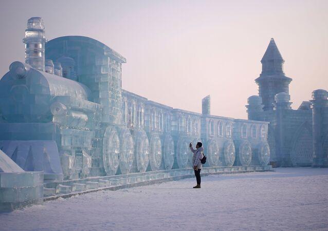 رجل يقف أمام منحوتة جليدية على شكل قطار، في إطار مهرجان هاربن الدولي السنوي للمنحوتات الثلجية في مدينة هاربن، الصين 5 يناير 2020