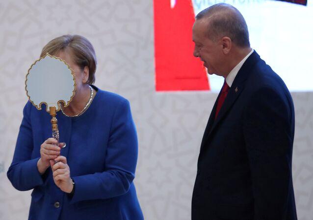 المستشارة الألمانية أنغيلا ميركل تعبر عن سعادتها بالهدية التي قدمها لها الرئيس التركي رجب طيب أردوغان خلال مراسم افتتاح المباني الجديدة للجامعة التركية – الألمانية في إسطنبول، 24 يناير 2020