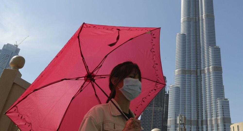 امرأة ترتدي قناعا واقيا في دبي، تلتقط صورة على خلفية برج خليفة، بعد تأكيد حالات الإصابة بفيروس كورونا في الإمارات العربية المتحدة 30 يناير 2020