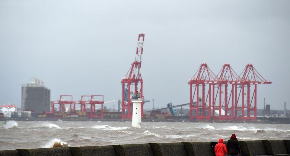 ناس يمشون على طول الكورنيش بينما تتأرجح الأمواج في مصب نهر ميرسي، مقابل ميناء ليفربول للحاويات، شمال غرب إنجلترا، تزامنا مع اجتياح عاضقة سيارة للبلاد، 9 فبراير/ شباط 2020