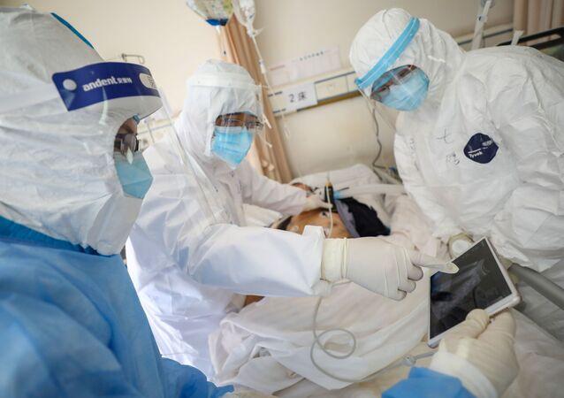 أطباء يرتدون سترات واقية يوقعون الكشف الطبي على مريض مصاب بفيروس كورونا داخل جناح منعزل بمستشفى ووهان الصيني