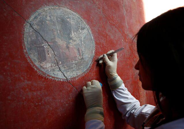 عالم آثار يعمل على لوحة جدارية في منزل العشاق (Casa degli Amanti) ، أحد ثلاثة منازل تم ترميمها (منازل قديمة)، أعيد فتحها أمام الجمهور في الموقع الأثري بومبي، إيطاليا 18 فبراير 2020