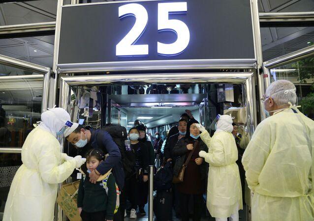 موظفو وزارة الصحة السعودية يقومون بفحص المسافرين القادمين من الصين لدى وصولهم إلى مطار الملك خالد الدولي في الرياض لمنع فيروس كورونا الجديد