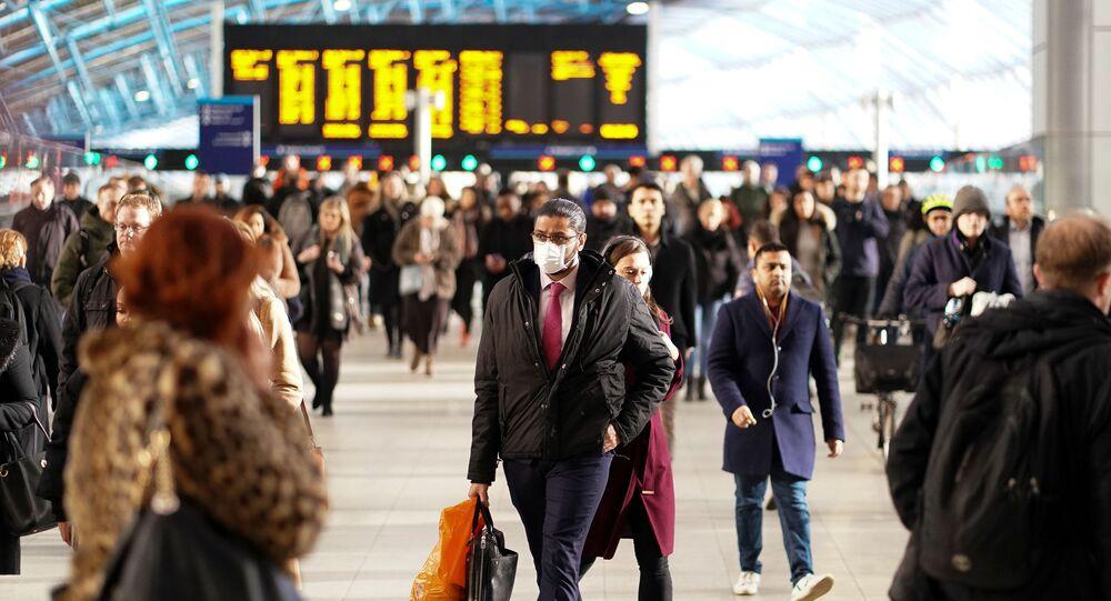 رجل يرتدي قناعا للوجه في محطة واترلو في لندن