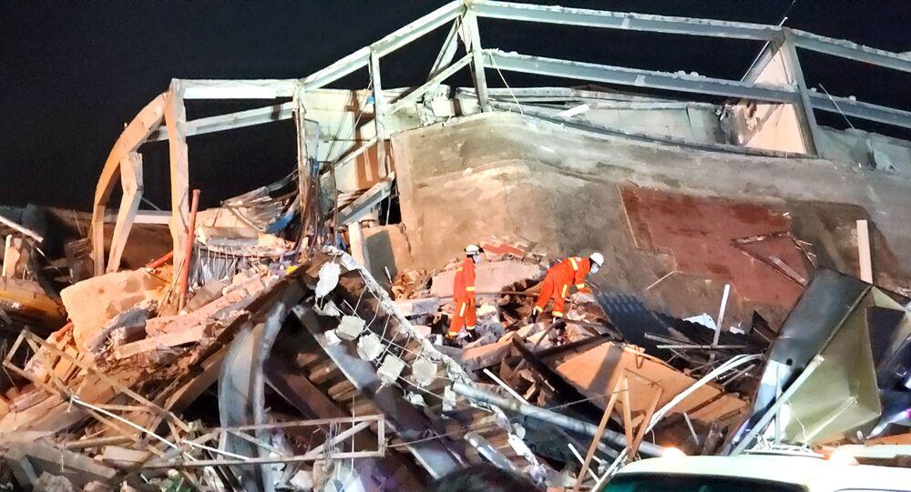 عمال الإنقاذ في موقع انهيار فندق كان يستخدم للحجر الصحي من فيروس كورونا في مدينة تشيوانتشو الساحلية شرقي الصين
