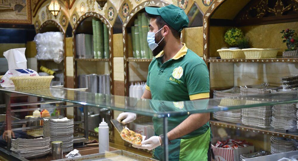 في محلات الطعام.. سوريون يرتدون الأقنعة الواقية في دمشق كوقاية من كورونا