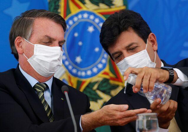 الرئيس البرازيلي جاير بولسونارو ووزير الصحة لويز إنريكي مانديتاس، يرتديان أقنعة واقية، ويعقمان أيديهما خلال مؤتمر صحفي للإعلان عن اجراءات احترازية للحد من انتشار مرض الفيروس التاجي (COVID-19) في البرازيل، البرازيل، 18 مارس 2020.
