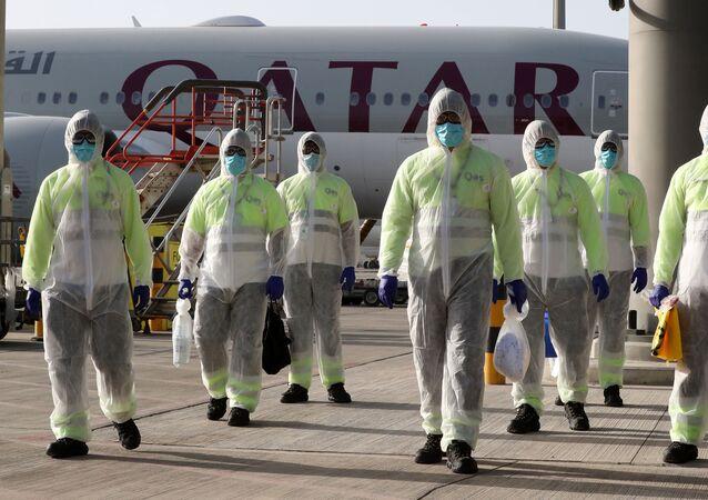 موظفو شركة قطر لخدمات الطيران يرتدون ملابس واقية كإجراء سلامة أثناء فيروس كورونا