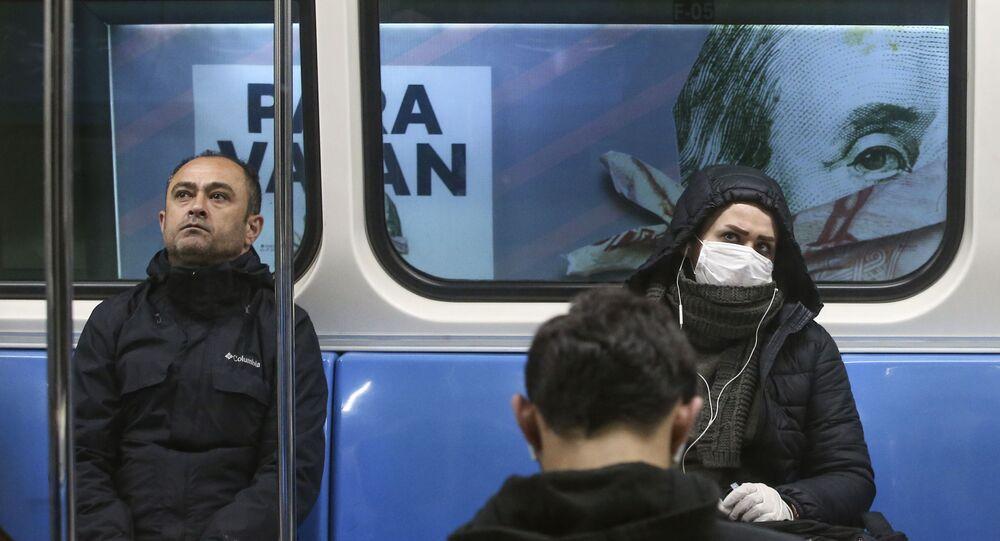 ركاب في مترو، بعضهم يرتدون أقنعة واقية، خلفهم لوحة إعلانات لكتاب يظهر على غلافه صورة للرئيس الأمريكي بنجامين فرانكلين على ورقة نقدية فئة 100 دولار أمريكي، وسط اسطنبول، تركيا  25 مارس 2020