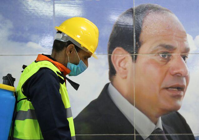 أحد أعضاء الفريق الطبي بجانب لافتة للرئيس المصري عبد الفتاح السيسي أثناء قيامه برش مطهر في محطة مترو الشهداء بالقاهرة كورونا - مصر