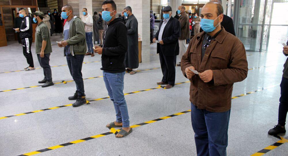 مواطنون يرتدون كمامات طبية كجزء من اجراءات وقائية مرض فيروس كورونا (كوفيد-19)، وهم يقفون على بعد مسافة آمنة وفق معايير منظمة الصحة العالمية، في طوابير في أحد البنوك في مصراتة، ليبيا  22 مارس / آذار 2020