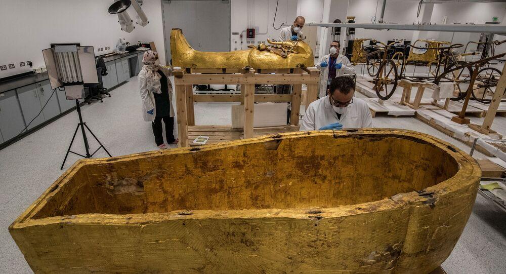 علماء آثار مصريون يرتدون الكمامات الحماية  من عدوى كورونا، خلال ترميم التابوت الذهبي للفرعون توت عنخ آمون (الذي حكم بين 1342 إلى 1325 ق.م.) في معمل الترميم بالمتحف المصري الكبير، الذي شيد حديثا في الجيزة بضواحي  القاهرة ، 13 أبريل 2020.