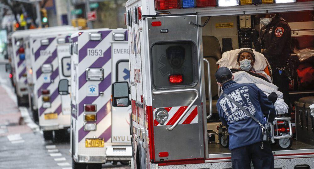 مريض يصل بسيارة إسعاف برعاية عاملين طبيين يرتدون معدات وقائية بسبب مخاوف كوفيد-19  خارج مركز جامعة نيويورك لانغون الطبي، 13 أبريل 2020 ، في نيويورك، الولايات المتحدة