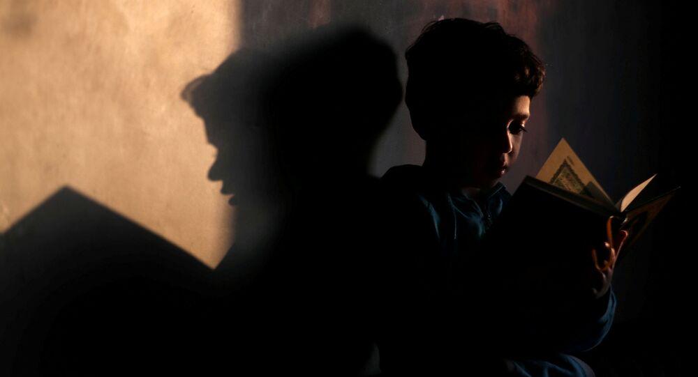 صبي يقرأ القرآن في منزله في القاهرة، شهر رمضان، مصر 26 أبريل 2020