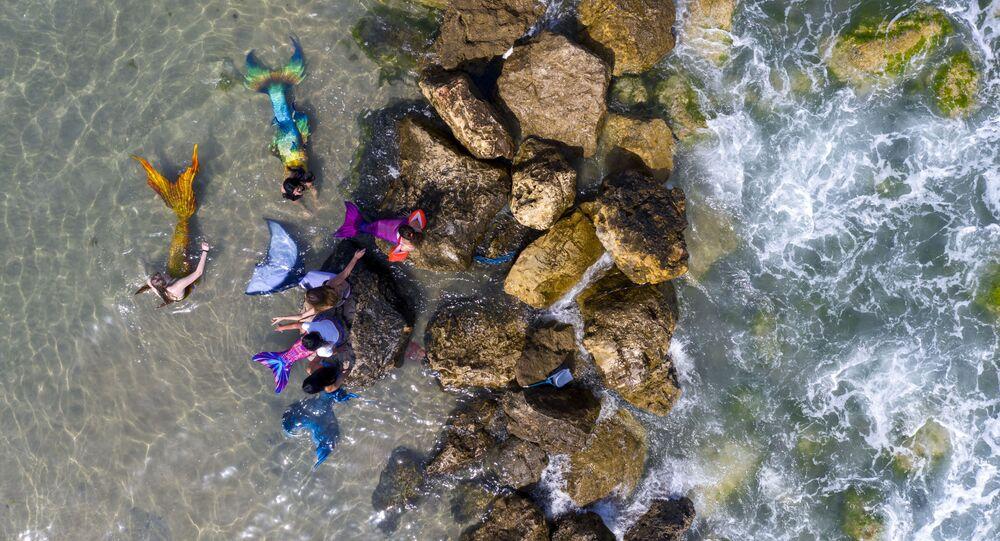أعضاء جماعة حوريات البحر الإسرائيلية يرتدون ذيل عروس البحر على شاطئ البحر في بات يام، بالقرب من تل-أبيب، إسرائيل، 23 مايو/ أيار 2020.