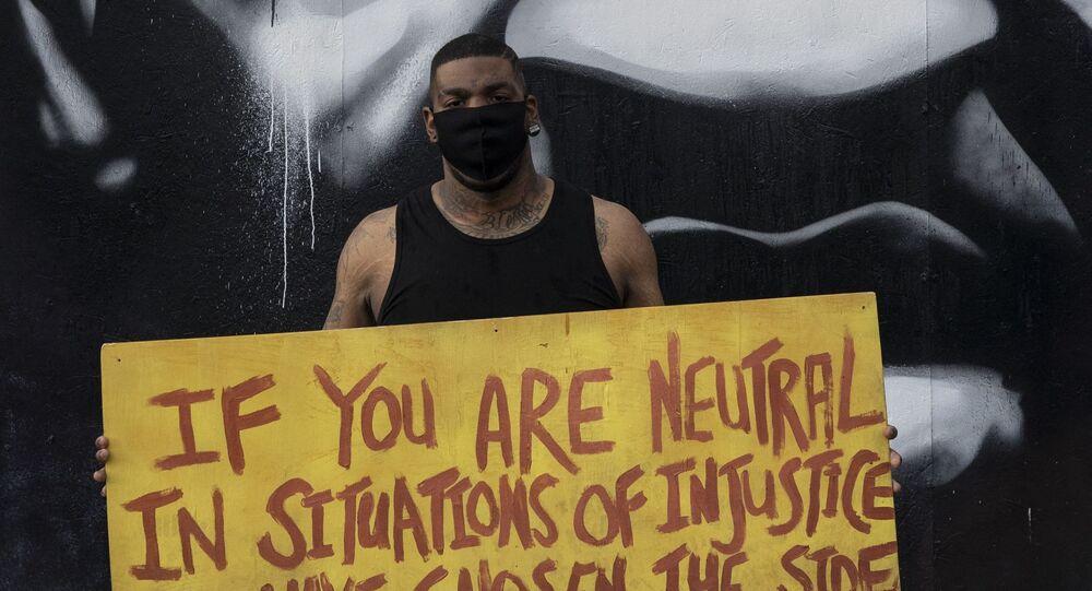 رجل يقف على خلفية جدارية المواطن الأمريكي من أصول أفريقية، جورج فلويد، ويحمل لافتة كتب عليها (إذا كنت محايداً في قضية ظالمة، فأنت إخترت جانب المضطهد) في مينيابوليس، بولاية مينيسوتا،2 يونيو 2020