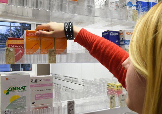 صيدلانية تزيل علب أدوية فيتامين Uvesterol D من رف في صيدلية في بوردو، جنوب غرب فرنسا، 4 يناير/ كانون الثاني 2017