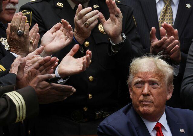 الرئيسالأمريكي دونالد ترامب وسط التصفيق بعد مراسم التوقيع على أمر تنفيذي فيما يخص الإصلاح بالشرطة، في فناء البيت الأبيض في واشنطن، الولايات المتحدة، 16 يونيو  2020